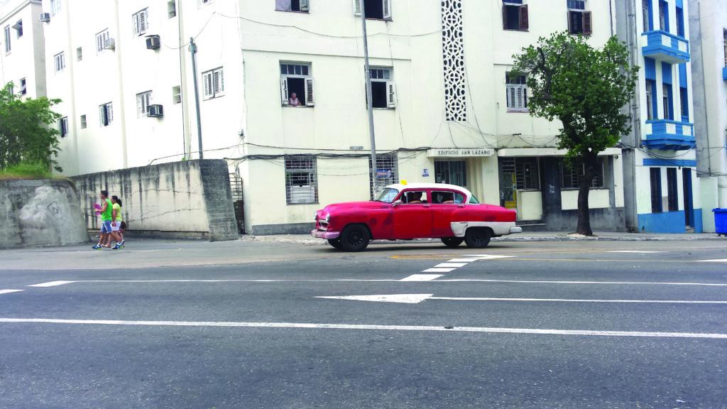A classic car cruises in front of la Universidad de La Habana.