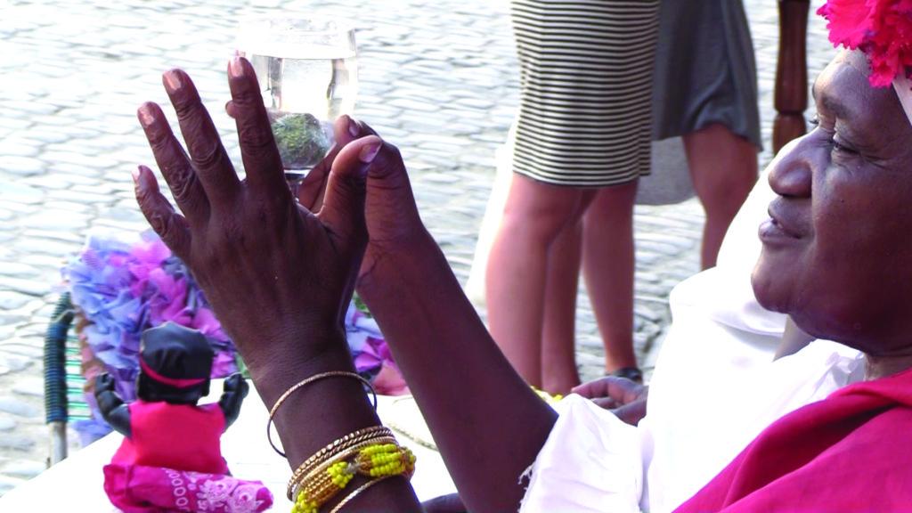 A Santeria priestess performs a divination in a square in Havana.